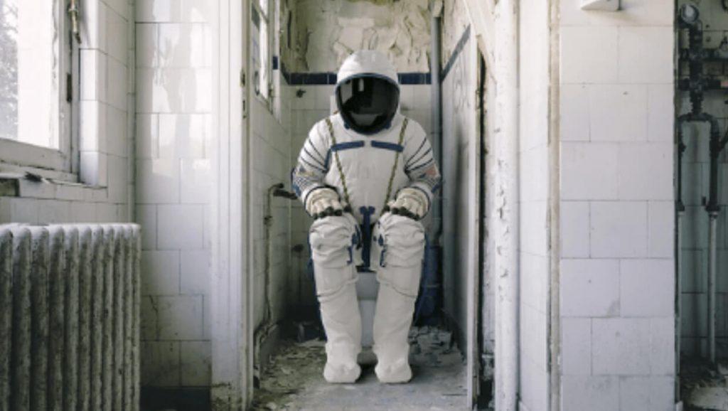 Spaceman sitting on a toilet